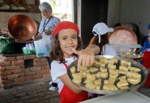 Crianças fazendo biscoitos na cozinha externa original. Olha os tachos de cobre lá no fundo!